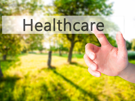 mandated: Healthcare - Hand pressing a button on blurred background concept . Business, technology, internet concept. Stock Photo