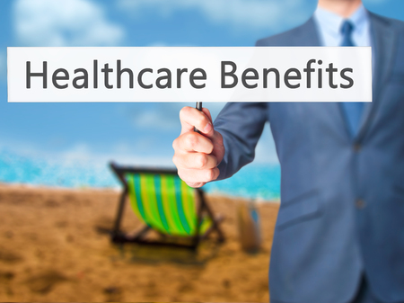 medicaid: Healthcare Benefits - Businessman hand holding sign. Business, technology, internet concept. Stock Photo