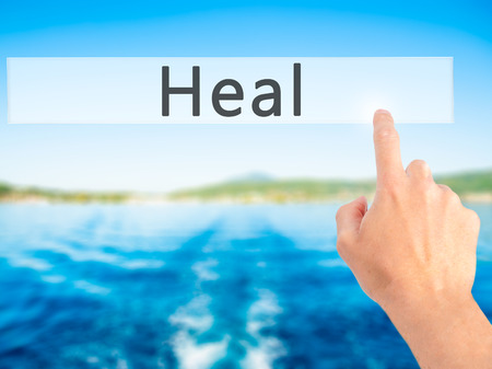 soulful: Heal - Hand pressing a button on blurred background concept . Business, technology, internet concept. Stock Photo Stock Photo