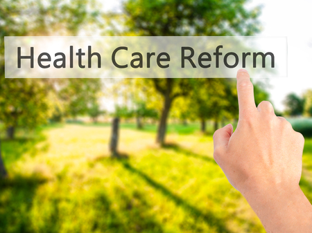 Health Care Reform - Hand pressing a button on blurred background concept . Business, technology, internet concept. Stock Photo Stock Photo