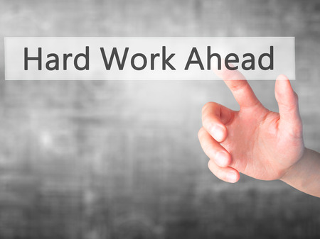 hard work ahead: Hard Work Ahead - Hand pressing a button on blurred background concept . Business, technology, internet concept. Stock Photo