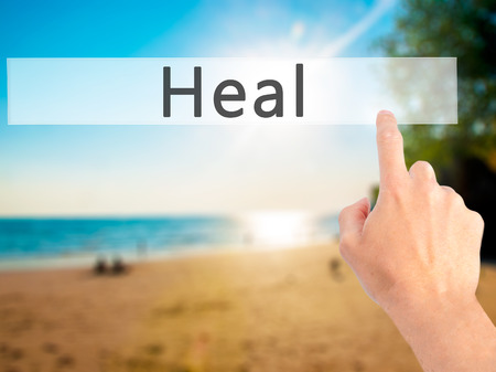 complementary therapies: Heal - Hand pressing a button on blurred background concept . Business, technology, internet concept. Stock Photo Stock Photo