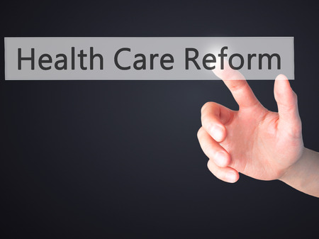 health reform: Health Care Reform - Hand pressing a button on blurred background concept . Business, technology, internet concept. Stock Photo