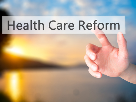 obama care: Health Care Reform - Hand pressing a button on blurred background concept . Business, technology, internet concept. Stock Photo