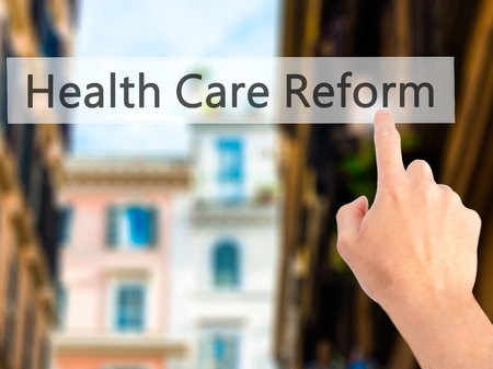 hmo: Health Care Reform - Hand pressing a button on blurred background concept . Business, technology, internet concept. Stock Photo