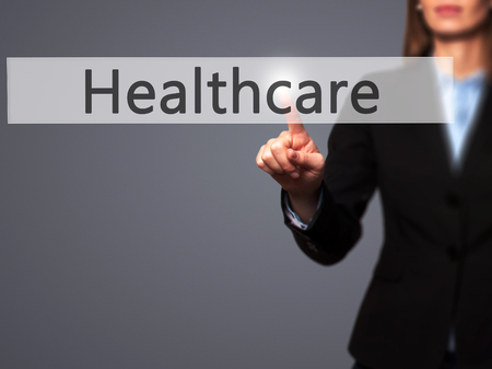 premiums: Healthcare - Businesswoman hand pressing button on touch screen interface. Business, technology, internet concept. Stock Photo Stock Photo