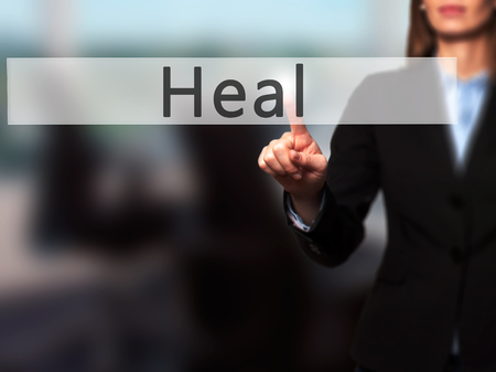 soulful: Heal - Businesswoman hand pressing button on touch screen interface. Business, technology, internet concept. Stock Photo