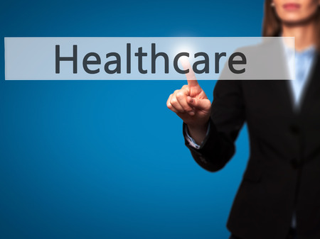 Healthcare - Businesswoman hand pressing button on touch screen interface. Business, technology, internet concept. Stock Photo Stock Photo