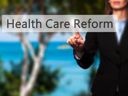 health reform: Health Care Reform - Businesswoman hand pressing button on touch screen interface. Business, technology, internet concept. Stock Photo