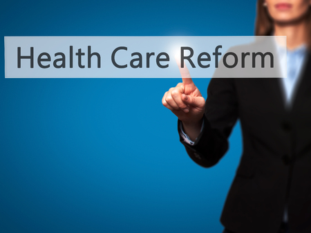 obama care: Health Care Reform - Businesswoman hand pressing button on touch screen interface. Business, technology, internet concept. Stock Photo