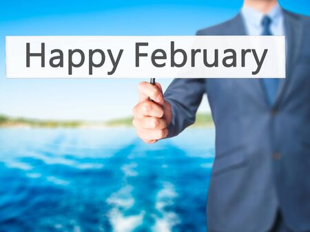 january 1: Happy February - Businessman hand holding sign. Business, technology, internet concept. Stock Photo