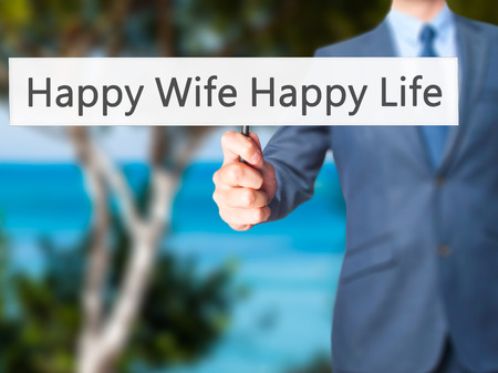 wedlock: Happy Wife Happy Life - Businessman hand holding sign. Business, technology, internet concept. Stock Photo