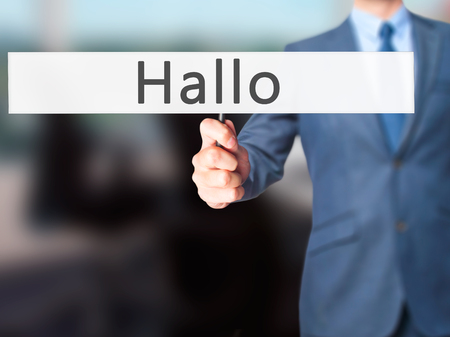 hallo: Hallo (Hello in German) - Businessman hand holding sign. Business, technology, internet concept. Stock Photo