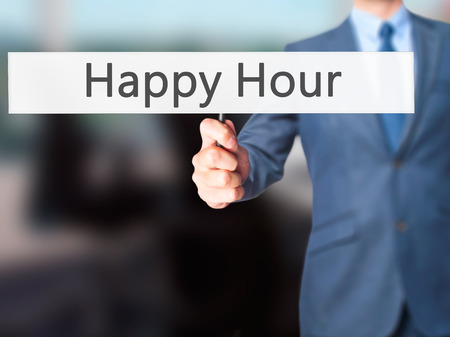 happyhour: Happy Hour - Businessman hand holding sign. Business, technology, internet concept. Stock Photo Stock Photo