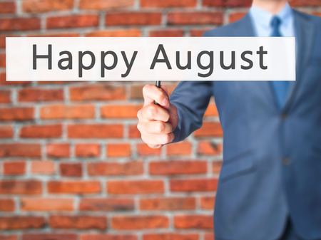 august: Happy August - Businessman hand holding sign. Business, technology, internet concept. Stock Photo