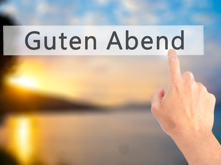 cansancio: Guten Abend (Good Evening in German) - Hand pressing a button on blurred background concept . Business, technology, internet concept. Stock Photo