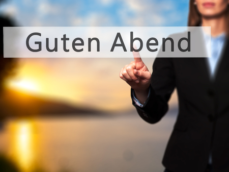 cansancio: Guten Abend (buena tarde en alemán) - pulsar el botón mano de la empresaria en la interfaz de pantalla táctil. Negocios, la tecnología, el concepto de internet. Foto de stock