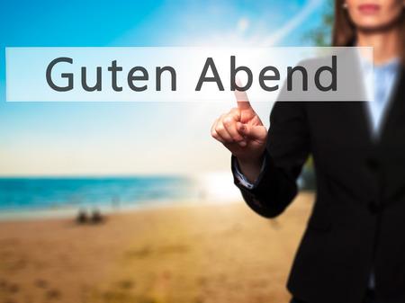 good evening: Guten Abend (Good Evening in German) - Businesswoman hand pressing button on touch screen interface. Business, technology, internet concept. Stock Photo