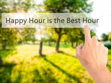 hour hand: Happy Hour is the Best Hour - Hand pressing a button on blurred background concept . Business, technology, internet concept. Stock Photo