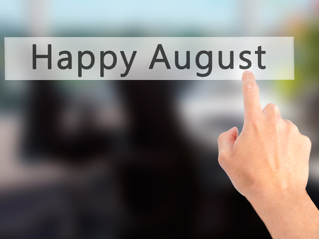 august: Happy August - Hand pressing a button on blurred background concept . Business, technology, internet concept. Stock Photo Stock Photo