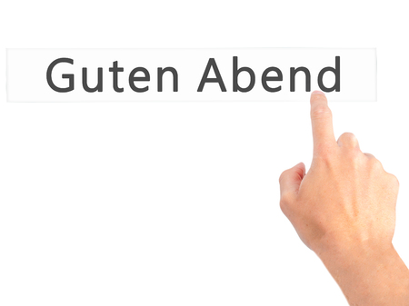 weekdays: Guten Abend (Good Evening in German) - Hand pressing a button on blurred background concept . Business, technology, internet concept. Stock Photo