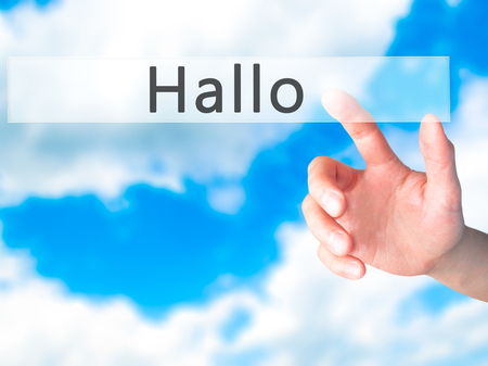hallo: Hallo (Hello in German) - Hand pressing a button on blurred background concept . Business, technology, internet concept. Stock Photo