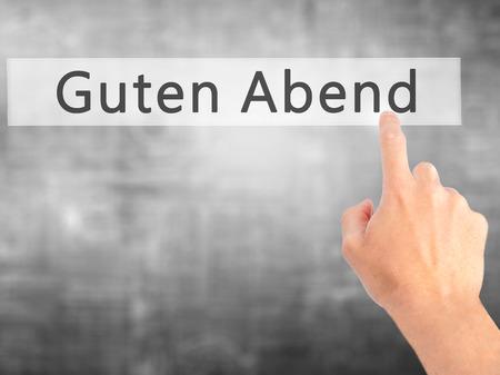cansancio: Guten Abend (buena tarde en alem�n) - Mano presionando un bot�n en concepto de fondo borroso. Negocios, la tecnolog�a, el concepto de internet. Foto de stock
