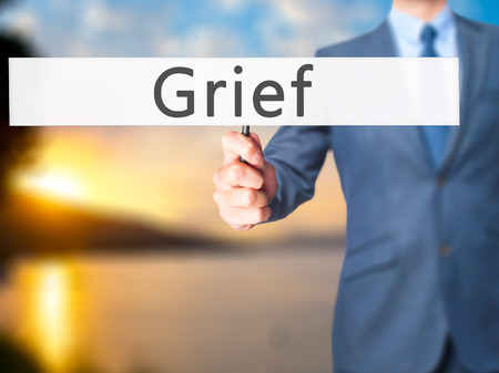 dolor: Grief - Businessman hand holding sign. Business, technology, internet concept. Stock Photo