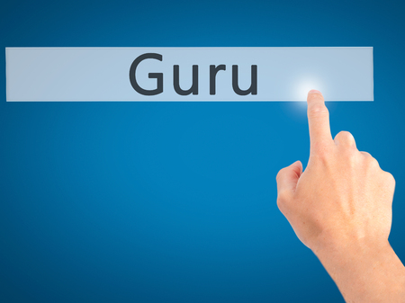 Guru - Hand pressing a button on blurred background concept . Business, technology, internet concept. Stock Photo