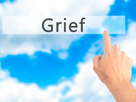vexation: Grief - Hand pressing a button on blurred background concept . Business, technology, internet concept. Stock Photo Stock Photo