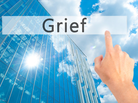 lamentation: Grief - Hand pressing a button on blurred background concept . Business, technology, internet concept. Stock Photo Stock Photo