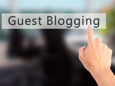 optimizer: Guest Blogging - Hand pressing a button on blurred background concept . Business, technology, internet concept. Stock Photo