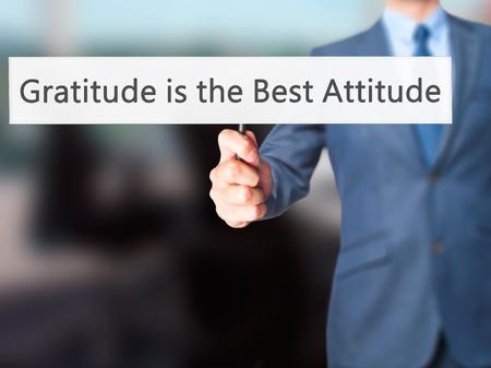 positiveness: Gratitude is the Best Attitude - Businessman hand holding sign. Business, technology, internet concept. Stock Photo