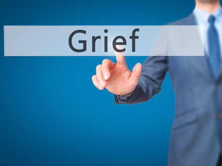 Grief - Businessman hand pressing button on touch screen interface. Business, technology, internet concept. Stock Photo