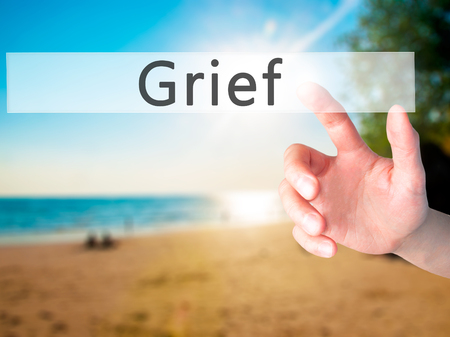 Grief - Hand pressing a button on blurred background concept . Business, technology, internet concept. Stock Photo Stock Photo