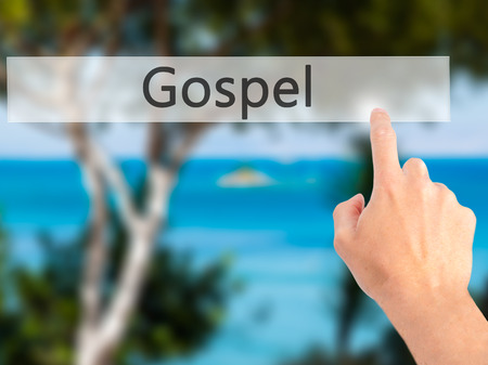 gospel: Gospel - Hand pressing a button on blurred background concept . Business, technology, internet concept. Stock Photo