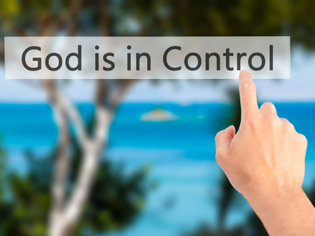 god button: God is in Control - Hand pressing a button on blurred background concept . Business, technology, internet concept. Stock Photo Stock Photo