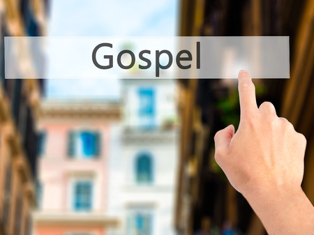 Gospel - Hand pressing a button on blurred background concept . Business, technology, internet concept. Stock Photo