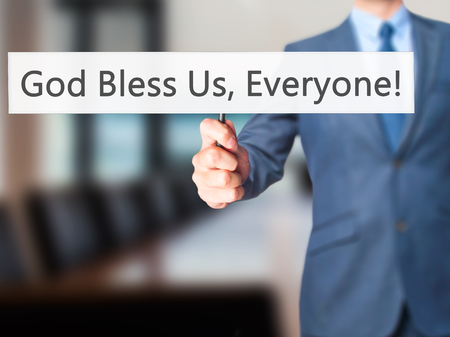preachment: God Bless Us, Everyone - Businessman hand holding sign. Business, technology, internet concept. Stock Photo Stock Photo