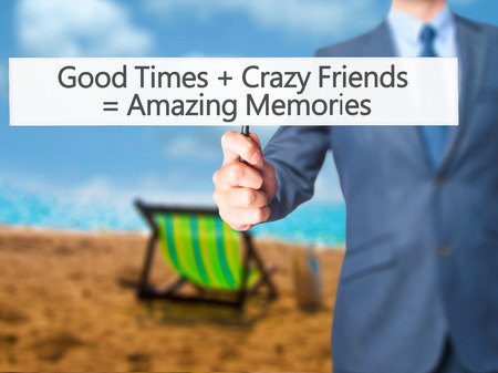 positiveness: Good Times  Crazy Friends  Amazing Memories - Businessman hand holding sign. Business, technology, internet concept. Stock Photo