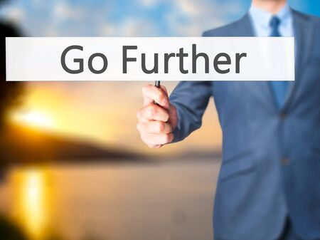 risks ahead: Go Further - Businessman hand holding sign. Business, technology, internet concept. Stock Photo