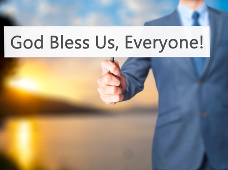 god bless: God Bless Us, Everyone - Businessman hand holding sign. Business, technology, internet concept. Stock Photo Stock Photo