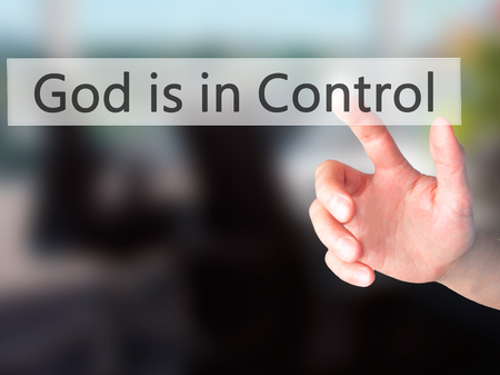 confessing: God is in Control - Hand pressing a button on blurred background concept . Business, technology, internet concept. Stock Photo Stock Photo
