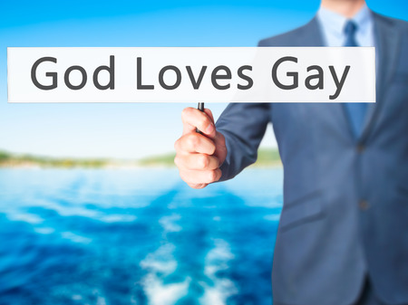 loves: God Loves Gay - Businessman hand holding sign. Business, technology, internet concept. Stock Photo Stock Photo
