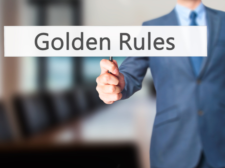 golden rule: Golden Rules - Businessman hand holding sign. Business, technology, internet concept. Stock Photo Stock Photo