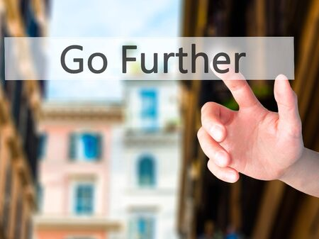 Go Further - Hand pressing a button on blurred background concept . Business, technology, internet concept. Stock Photo