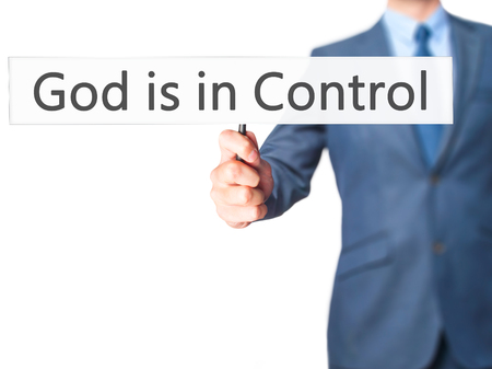 confessing: God is in Control - Businessman hand holding sign. Business, technology, internet concept. Stock Photo