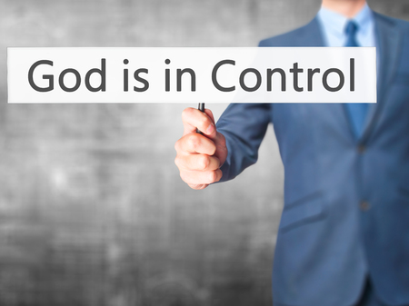 sanctification: God is in Control - Businessman hand holding sign. Business, technology, internet concept. Stock Photo