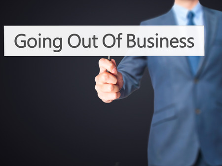 liquidation: Going Out Of Business - Businessman hand holding sign. Business, technology, internet concept. Stock Photo