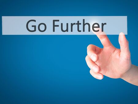 further: Go Further - Hand pressing a button on blurred background concept . Business, technology, internet concept. Stock Photo